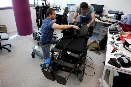 Employees work on a wheelchair developed by Israeli company UPnRIDE Robotics, that enables paralysed people with limited function in their arms to stand upright, during a demonstration at their offices in Yoqneam, Israel September 6, 2016. REUTERS/Baz Ratner