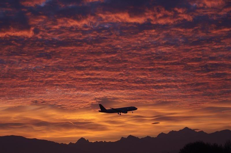 A Brussels Airlines aircraft prepares for landing in Cointrin airport during sunrise over the Mont Blanc in Geneva