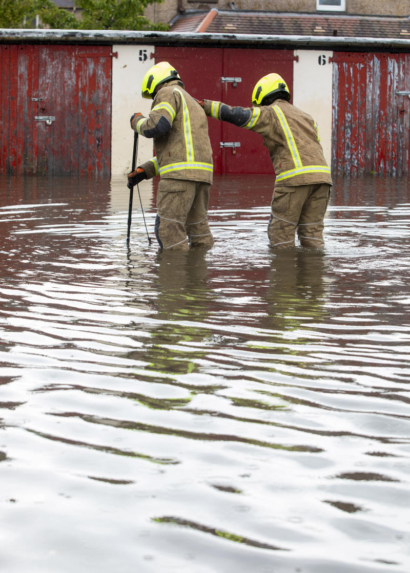 Fire brigade officers look for a blocked drain which has flooded a car park leaving one car flooded in Barnton, Edinburgh, as heavy rains hits most of the country
