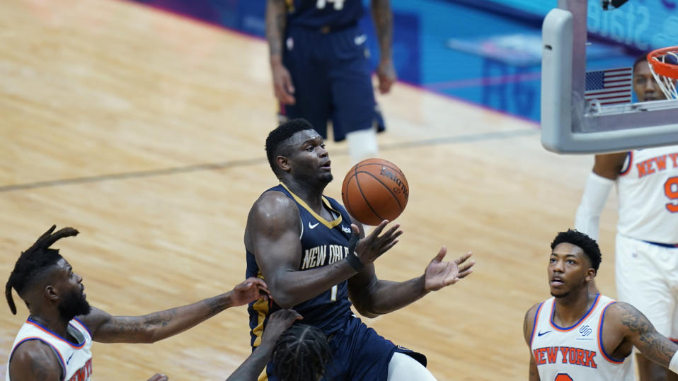 New Orleans Pelicans forward Zion Williamson (1) is fouled as he drives to the basket between New York Knicks forward Reggie Bullock, left, and guard Elfrid Payton in the second half of an NBA basketball game in New Orleans, Wednesday, April 14, 2021. (AP Photo/Gerald Herbert)