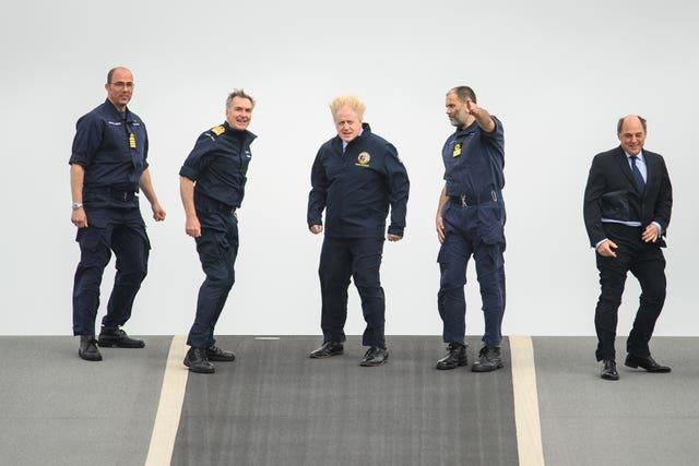 (Left to right) Captain Angus Essenhigh, First Sea Lord Admiral Tony Radakin, Prime Minister Boris Johnson, Commodore Steve Moorhouse and Defence Secretary Ben Wallace face strong winds as they walk on the flight deck