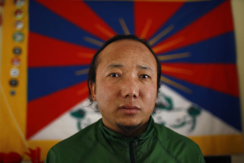 In this Wednesday, April 2, 2014 photo, Sonam Tashi sits in front of a Tibetan flag at the Tibetan refugee camp in Katmandu, Nepal. Tashi said he and another Tibetan Sonam Chodon were held for weeks after being picked up by police who broke up a small rally in front of the Chinese Embassy visa office on March 10 and were released only this week without charges or access to legal aid in a sign that authorities are bowing to pressure from China. The government on Thursday denied accusations in a report by Human Rights Watch that it is mistreating Tibetans. Nearly 20,000 Tibetans who fled their homeland now live in Nepal. (AP Photo/Niranjan Shrestha)