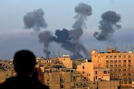 A Palestinian boy watches smoke billowing from targets during Israeli air strikes on the southern Gaza region of Khan Yunis on May 11, 2021