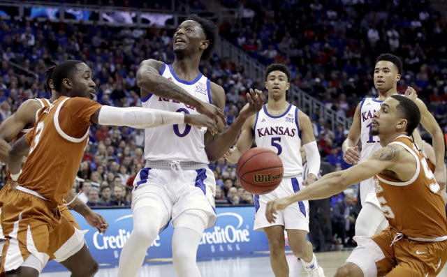 Texas' Courtney Ramey, left, and Kamaka Hepa, right, strip the ball from Kansas' Marcus Garrett (0) during the first half of an NCAA college basketball game in the Big 12 men's tournament Thursday, March 14, 2019, in Kansas City, Mo. (AP Photo/Charlie Riedel)
