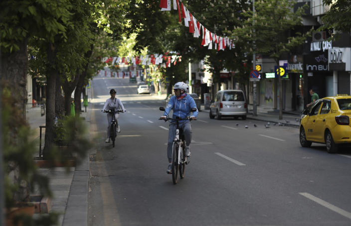 People ride bicycles on a deserted road during a lockdown, in Ankara, Turkey, Saturday, May 15, 2021. Turkey is in the final days of a full lockdown and the government has ordered people to stay home and businesses to close amid a huge surge in infections. But millions of workers are exempt and so are foreign tourists. (AP Photo/Burhan Ozbilici)