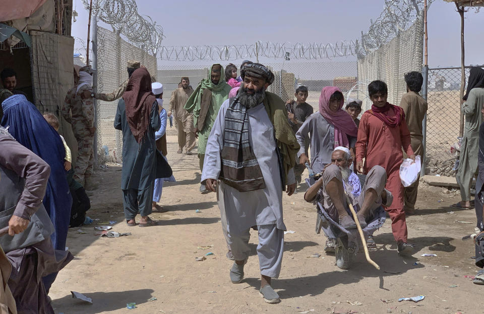 Afghan people enter into Pakistan through a border crossing point, in Chaman, Pakistan, Friday, Aug. 20, 2021. Chaman, is a key border crossing between Pakistan and Afghanistan, normally thousands of Afghans and Pakistanis cross daily and a steady stream of trucks passes through, taking goods to Afghanistan. (AP Photo)