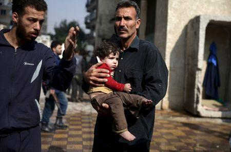A man carries an injured child as another man gestures at a site hit by missiles fired by Syrian government forces on a busy marketplace in the Douma neighborhood of Damascus, Syria October 30, 2015. REUTERS/Bassam Khabieh