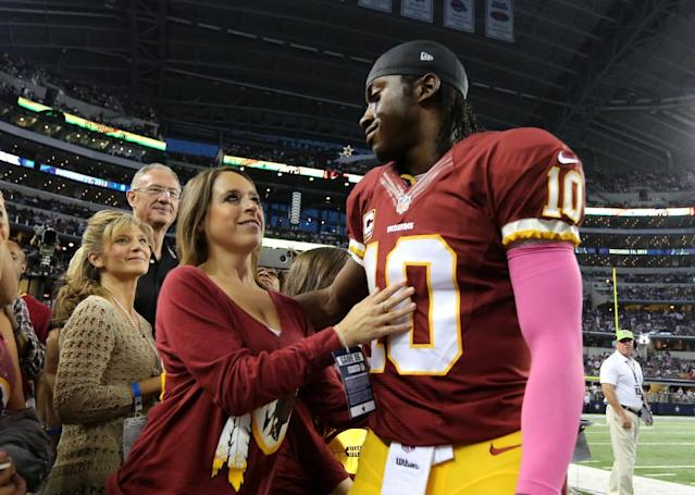 Washington Redskins quarterback Robert Griffin III (10) hugs his wife Rebecca Liddicoat, left, after warming up before an NFL football game against the Dallas Cowboys, Sunday, Oct. 13, 2013, in Arlington, Texas. (AP Photo/LM Otero)