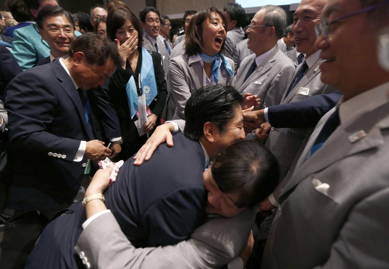 Prime Minister Shinzo Abe of Japan (C) celebrates with members of the Tokyo bid committee after Jacques Rogge, president of the International Olympic Committee (IOC), announced Tokyo as the city to host the 2020 Summer Olympic Games during a ceremony in Buenos Aires September 7, 2013. REUTERS/Marcos Brindicci (ARGENTINA - Tags: SPORT OLYMPICS POLITICS)