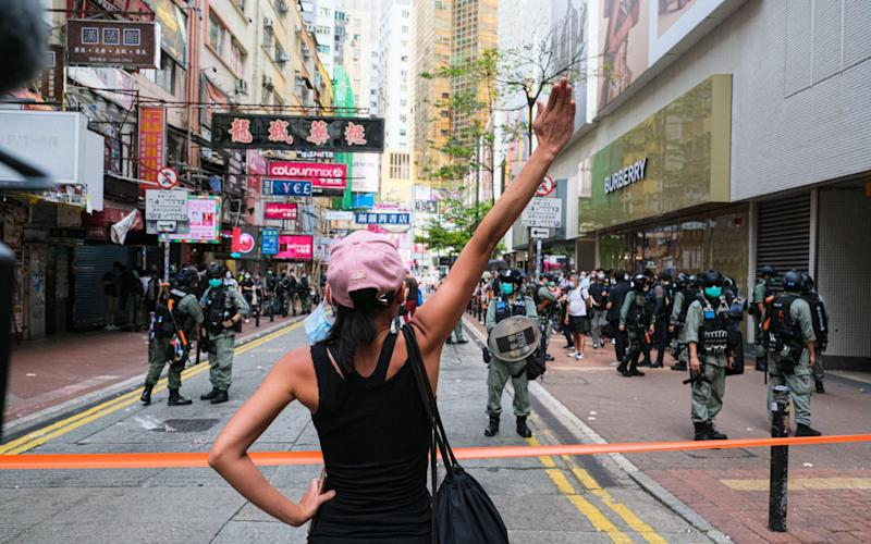 A girl holds up her hand to confront the police during a banned protest - Zuma/Alamy/Zuma/Alamy
