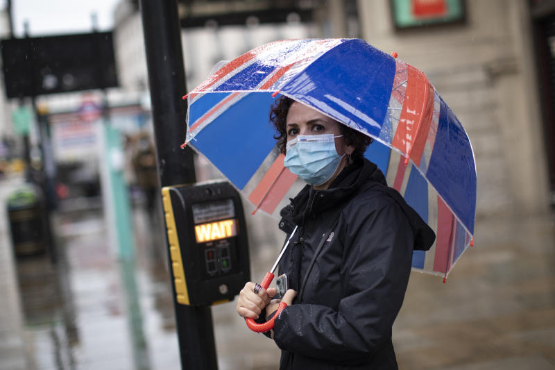 "LONDON, ENGLAND - OCTOBER 13: A woman walks near Piccadilly Circus wearing a face mask on October 13, 2020 in London, England. London Mayor Sadiq Khan said today that the city would move into Tier 2 of the government's new covid-19 risk classification once it hits 100 new daily cases per 100,000 people, which could happen this week. The second or ""high"" tier of the three-tier system triggers a ban on household mixing, although pubs would remain open. (Photo by Dan Kitwood/Getty Images)"