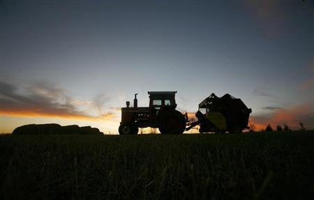 A tractor is silhouetted on a hillside in Prairie City