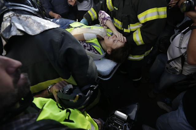 A journalist working for CNN is taken to an ambulance by emergency services after being injured in clashes between demostrators and mlitary police during a protest against the 2014 World Cup, in Sao Paulo June 12, 2014. REUTERS/Ricardo Moraes (BRAZIL - Tags: SPORT SOCCER WORLD CUP POLITICS CIVIL UNREST MEDIA)