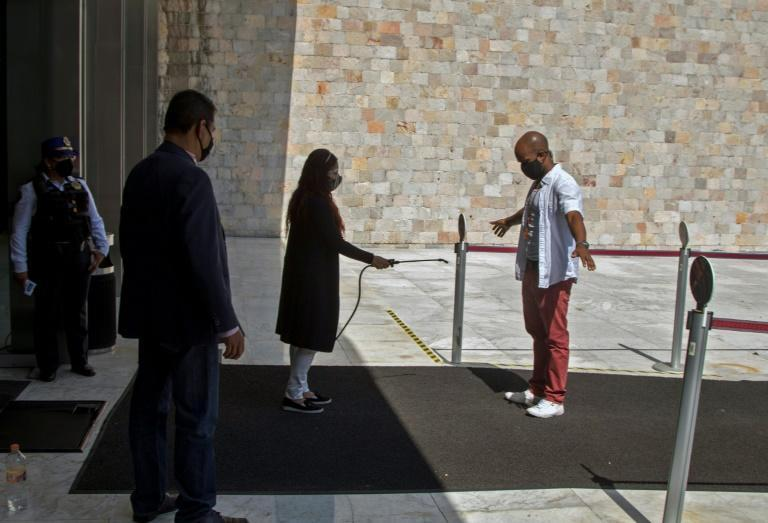 A worker sprays antibacterial liquid on a visitor at the entrance to the National Museum of Anthropology in Mexico City, on November 14, 2020, amid the COVID-19 coronavirus pandemic
