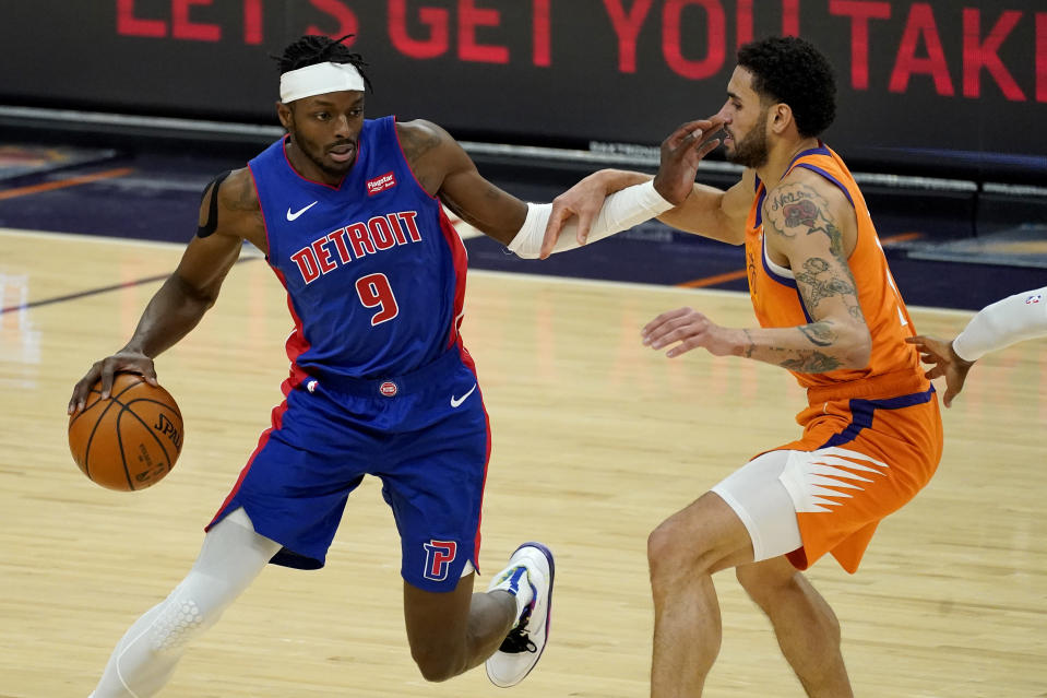 Detroit Pistons forward Jerami Grant (9) drives against Phoenix Suns forward Abdel Nader during the first half of an NBA basketball game, Friday, Feb. 5, 2021, in Phoenix. (AP Photo/Matt York)