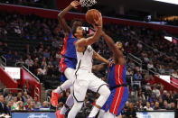 Brooklyn Nets guard Spencer Dinwiddie (8) drives on Detroit Pistons forward Sekou Doumbouya, left, and Andre Drummond, right, in the first half of an NBA basketball game in Detroit, Saturday, Jan. 25, 2020. (AP Photo/Paul Sancya)
