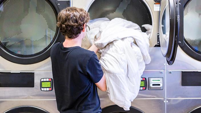 person doing laundry in laundromat