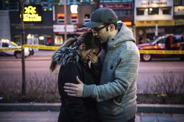 <p>Farzad Salehi consoles his wife, Mehrsa Marjani, who was at a nearby cafe and witnessed the aftermath when a van plowed down a crowded sidewalk, killing multiple people and injuring others, Monday, April 23, 2018, in Toronto. (Photo: Aaron Vincent Elkaim/The Canadian Press via AP) </p>