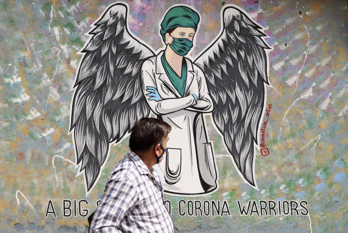 A man walks past a graffiti saluting frontline workers in the fight against the coronavirus pandemic in New Delhi, India, Wednesday, June 9, 2021. (AP Photo/Amit Sharma)