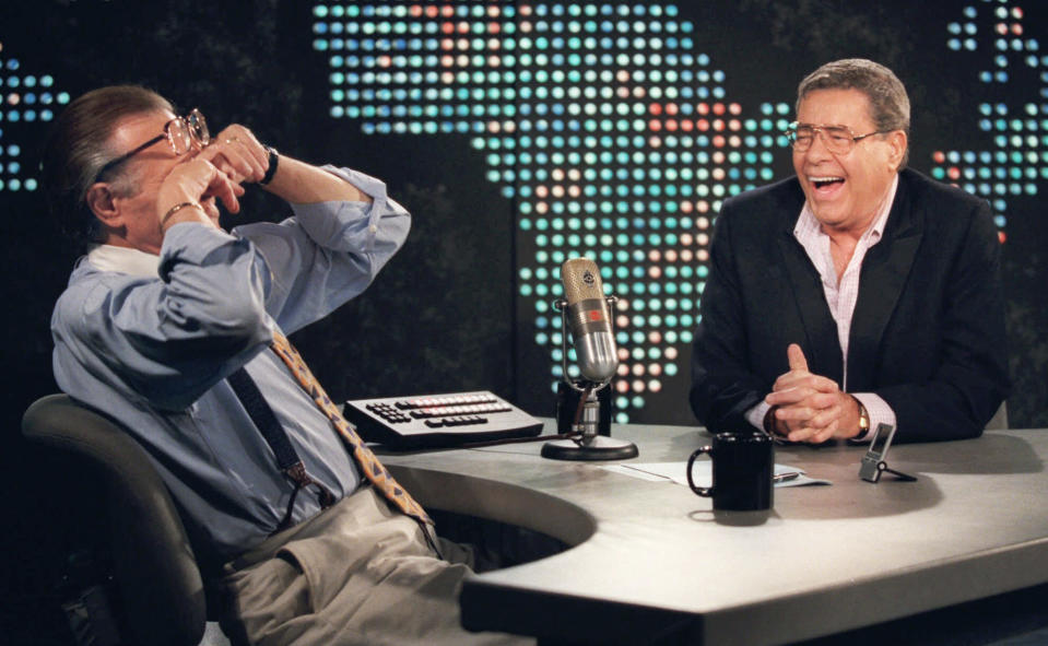 """FILE - In this Thursday, Aug. 26, 1999, file photo, talk show host Larry King wipes his eyes after laughing at a joke by comedy legend Jerry Lewis, on the set of """"Larry King Live"""" at CNN Studios in the Hollywood section of Los Angeles. King, who interviewed presidents, movie stars and ordinary Joes during a half-century in broadcasting, has died at age 87. Ora Media, the studio and network he co-founded, tweeted that King died Saturday, Jan. 23, 2021 morning at Cedars-Sinai Medical Center in Los Angeles. (AP Photo/Chris Pizzello, File)"""