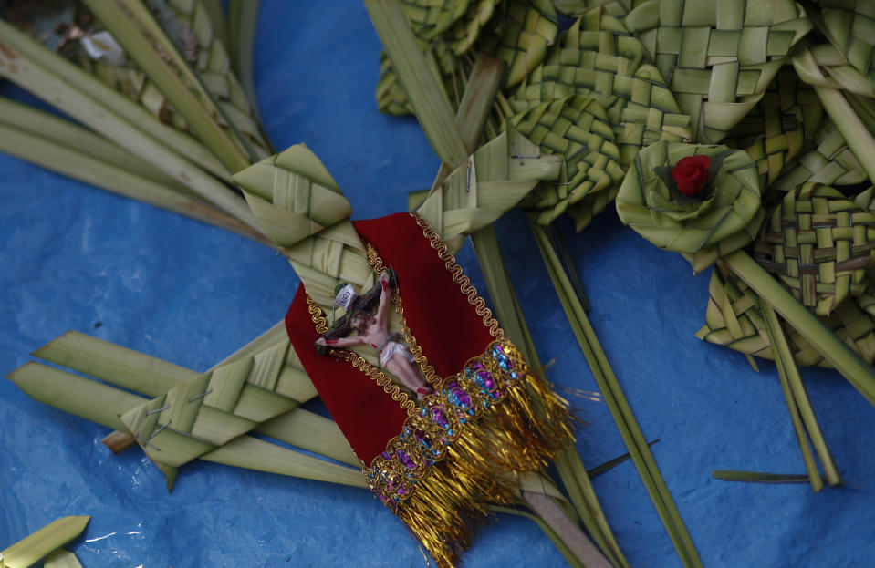 Palm fronds made into crosses decorated with Jesus Christ lay for sale outside the San Francisco Basilica in La Paz, Bolivia, Sunday, March 28, 2021. (AP Photo/Juan Karita)