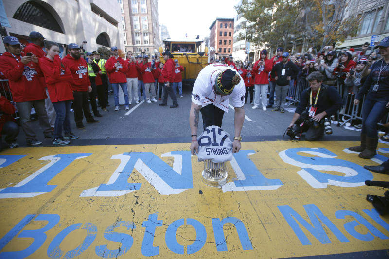 Boston Red Sox's Jonny Gomes places the championship trophy and a Red Sox baseball jersey at the Boston Marathon Finish Line during a pause in their World Series victory rolling rally in Boston, Saturday, Nov. 2, 2013 to remember those affected by the Marathon bombing. (AP Photo/Elise Amendola)