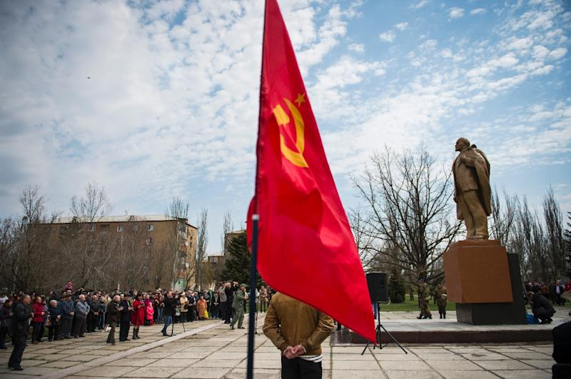 A Soviet Union flag flutters as people attend the unveiling of a Lenin statue in the town of Novoazovsk, in the self-proclaimed Donetsk People's Republic, in April 2015 (AFP Photo/Odd Andersen)