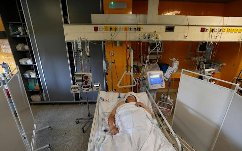 A Covid patient lies on a bed in an intensive care unit at Na Bulovce hospital in Prague, Czech Republic, as the country sees a surge in the number of patients hospitalised - AP