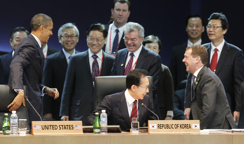 U.S. President Barack Obama, left, gets a reaction from Russian President Dmitry Medvedev, right, after jokingly covering up his microphone as they attend the opening plenary session at the Nuclear Security Summit at the Coex Center, in Seoul, South Korea, Tuesday, March 27, 2012. Sitting in the center is South Korean President Lee Myung-bak. (AP Photo/Pablo Martinez Monsivais)