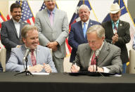 Texas Gov Greg Abbott signs Senate Bill 1, also known as the election integrity bill, into law with State Sen. Bryan Hughes, R-Mineola, front center left, looking on with others in the background in Tyler, Texas, Tuesday, Sept. 7, 2021. The sweeping bill signed Tuesday by the two-term Republican governor further tightens Texas' strict voting laws.(AP Photo/LM Otero)