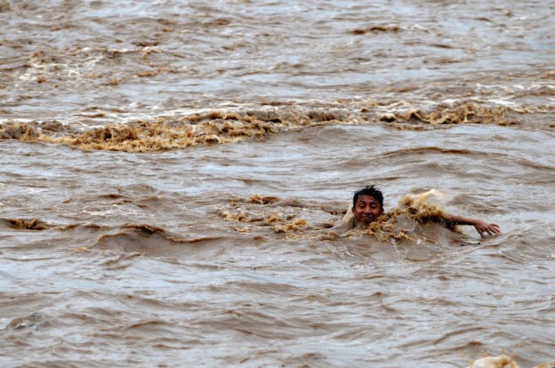 A boy tries to cross the overflowed Huiza River in La Libertad, 40 km south of San Salvador, on May 30, 2010 amid tropical storm Agatha, believed to be linked to El Nino (AFP Photo/Jose Cabezas)
