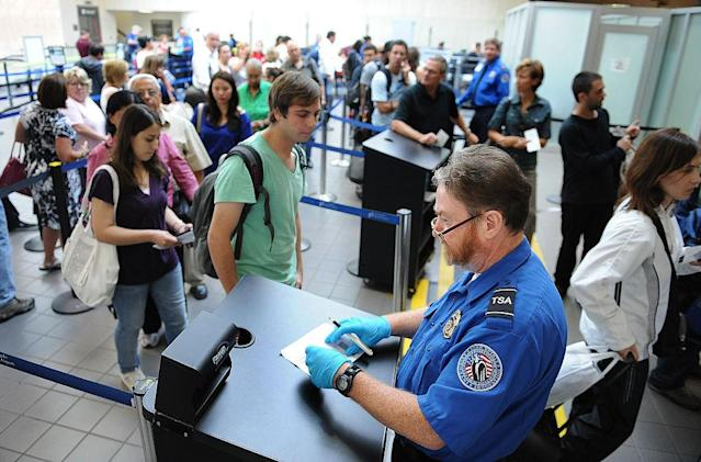 A TSA agent checks an ID under a Fraud Fighter machine at LAX. (Wally Skalij/Los Angeles Times)