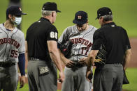 Houston Astros starting pitcher Jake Odorizzi has his belt inspected by first base umpire Ted Barrett (65) and home plate umpire Angel Hernandez, right, during the first inning of a baseball game against the Baltimore Orioles, Monday, June 21, 2021, in Baltimore. (AP Photo/Julio Cortez)