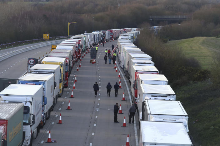 Drivers walk along the road next to freight lorries lined up on the M20 near Ashford, England, Friday Dec. 25, 2020. Thousands wait to resume their journey across The Channel after the borders with France reopened. Trucks inched slowly past checkpoints in Dover and headed across the Channel to Calais on Thursday after France partially reopened its borders following a scare over a rapidly spreading new virus variant. (Gareth Fuller/PA via AP)