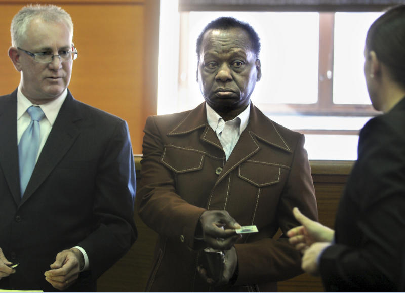 Onyango Obama, the uncle of President Barack Obama, surrenders his driving license in Framingham, Mass., District Court beside his attorney, F. Scott Bratton, left, Tuesday, March 27, 2012.  A Massachusetts drunken driving charge against him from an incident in August 2011 will be dismissed if he stays out of trouble for a year, officials said. Obama did not plead guilty, but acknowledged Massachusetts prosecutors had enough evidence to convict him. (AP Photo/MetroWest Daily News, Allan Jung)