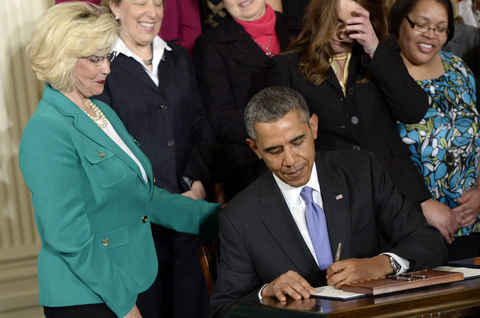 President Barack Obama signs executive actions, with pending Senate legislation, aimed at closing a compensation gender gap that favors men, in the East Room of the White House in Washington, Tuesday, April 8, 2014, during an event marking Equal Pay Day. Obama announced new executive actions to strengthen enforcement of equal pay laws for women. The president and his Democratic allies in Congress are making a concerted election-year push to draw attention to women's wages. Lilly Ledbetter watches at left. (AP Photo/Susan Walsh)