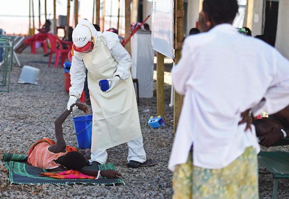 A health worker wearing protective equipment assists an Ebola patient at the Kenama treatment centre run on November 15, 2014 (AFP Photo/Francisco Leong)