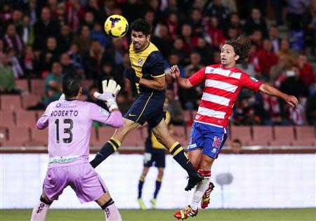 Atletico Madrid's Diego Costa (C) heads the ball next to Granada's Manuel Rolando Iturra (R) during their Spanish First Division soccer match at Nuevo Los Carmenes stadium in Granada October 31, 2013. REUTERS/Pepe Marin