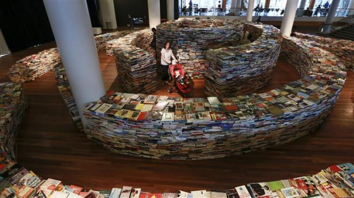 "Visitors walk in a labyrinth installation made up of 250,000 books titled ""aMAZEme"" by Marcos Saboya and Gualter Pupo at the Royal Festival Hall in central London July 31, 2012."