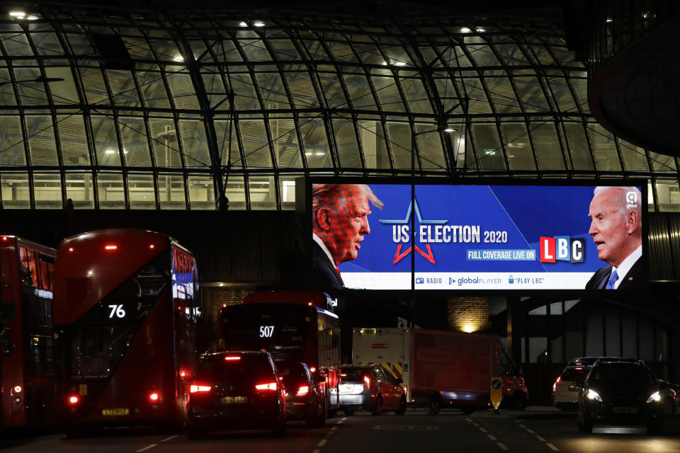 FILE - In this Nov. 2, 2020 file photo an advert screen in London, promotes the radio coverage of LBC (London Broadcasting Company) ahead of Tuesday's U.S. presidential election. If you're the leader of an increasingly isolated country, what's better — to keep an unreliable friend or gain a dependable critic? That's the dilemma facing British Prime Minister Boris Johnson over a U.S. election taking place weeks before the U.K. makes an economic split from the European Union at year's end and seeks new trade and diplomatic partners. (AP Photo/Matt Dunham, File)