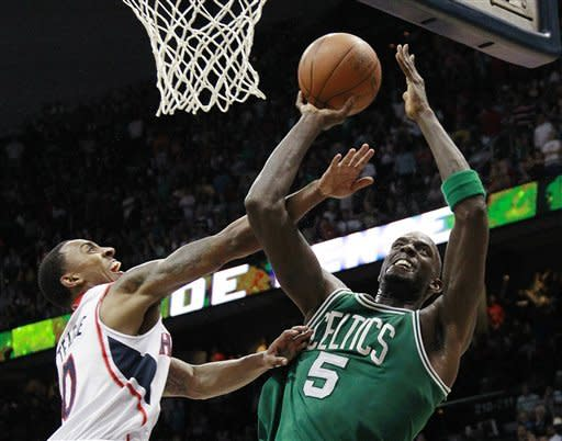 Boston Celtics' Kevin Garnett pulls down a rebound as Atlanta Hawks guard Jeff Teague (0) defends in the second half of Game 2 of an NBA first-round playoff basketball series, Tuesday, May 1, 2012, in Atlanta. Boston won 87-80 and evened the series at one game each. (AP Photo/John Bazemore)