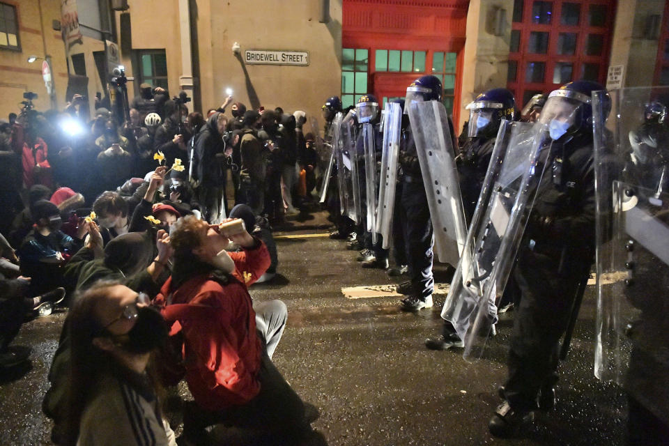 Protesters sit in front of police officers during the