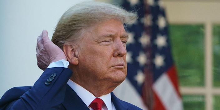 Donald Trump pats down his hair as he speaks during the Coronavirus Task Force daily briefing on COVID-19 in the Rose Garden of the White House in Washington, DC on March 30, 2020.