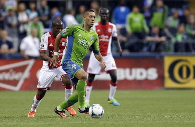 Seattle Sounders' Clint Dempsey, center, dribbles the ball as Portland Timbers' Darlington Nagbe, left, and Pa Modu Kah, right, look on, in the first half of a MLS soccer match, Sunday, Aug. 25, 2013, in Seattle. (AP Photo/Ted S. Warren)