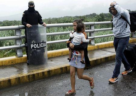 A woman carrying a child walks past a Colombian policeman after having crossed from Venezuela over the Simon Bolivar international bridge in Cucuta, Colombia February 13, 2018. REUTERS/Carlos Eduardo Ramirez