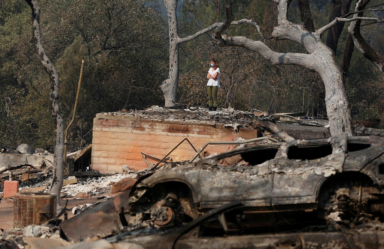 <p>Pamela Garibaldi looks over burned remains of her parents home destroyed by wildfire in Napa, Calif., Oct. 13, 2017. (Photo: Jim Urquhart/Reuters) </p>