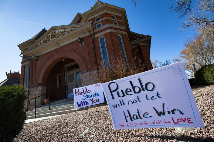 "FILE - In this Nov. 5, 2019, file photo, signs, flowers and candles expressing love for the Jewish community stand outside the Temple Emanuel in Pueblo, Colo. Richard Holzer, 28, was sentenced to nearly 20 years in prison on Friday, Feb. 26, 2021, for plotting to bomb the Colorado synagogue last year, by a judge who described the case as ""dripping with Nazism and supremacy."" (Christian Murdock/The Gazette via AP, File)"