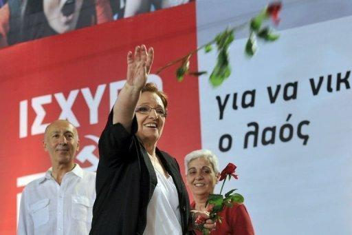 "Greek Communist party leader Aleka Papariga throws flowers to supporters during the party's main pre-election rally in Athens on June 15. Eurogroup chief Jean-Claude Juncker warned a radical left victory in Greece would have ""unpredictable"" consequences for the eurozone as Greeks fed up with austerity prepared for Sunday's elections"
