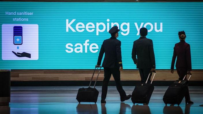 """Crew walking past a sign that reads """"keeping you safe"""" at Sydney Kingsford-Smith airport."""