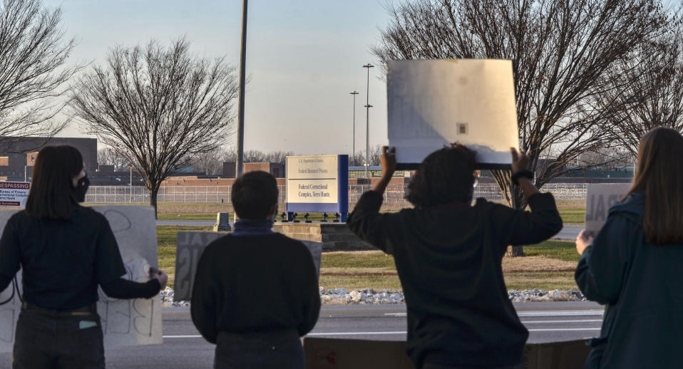 Protesters hold up signs on Prairieton Road across from the Federal Execution Chamber, Thursday, Dec. 10, 2020 in Terre Haute, Ind. The execution Brandon Bernard, convicted in the 1999 killing of two youth ministers in Texas is scheduled Thursday at the federal prison in Terre Haute, Indiana.. (Austen Leake/The Tribune-Star via AP)
